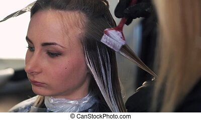 Stylist does hair coloring in beauty studio, woman changes...