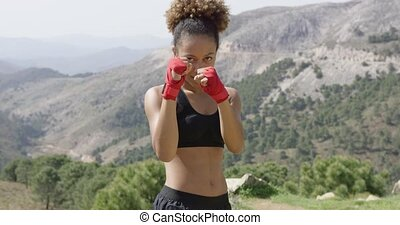 Smiling young female boxer - Pretty fit girl in red boxing...
