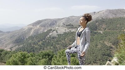 Young sportswoman on mountain - Side view of sportive woman...