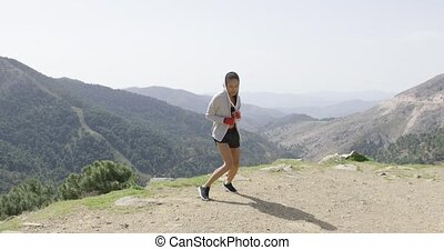 Young female kickboxer in mountains - Female in sportswear...