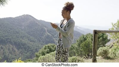 Young sportswoman using phone - Young beautiful woman...