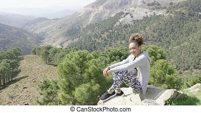 Smiling sportive woman on rock - Cheerful young woman in...