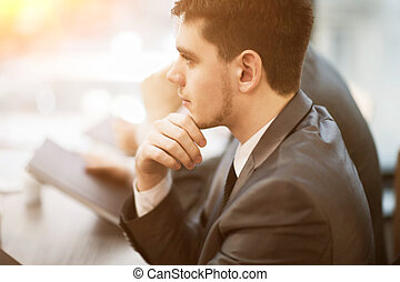 Casual businessman thinking with team behind him in office