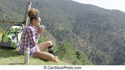 Young woman sitting ground and drinking - Young female...