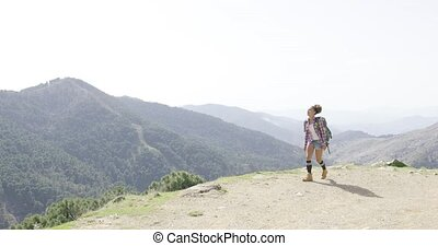 Female backpacker walking on top of mountain - Young woman...