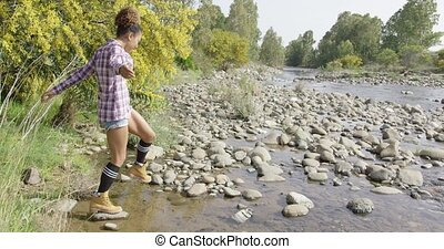 Female tourist walking on rocks - Young fit woman in casual...
