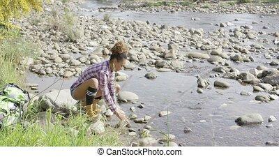 Female backpacker refreshing in creek - Young female...