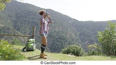 Young woman in VR glasses among mountains - Young female...