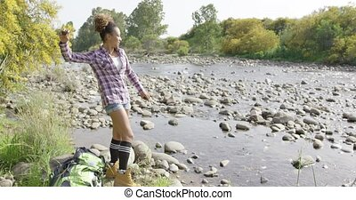 Young female backpacker throwing stones in river - Young...