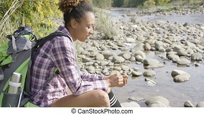 Female backpacker sitting near creek - Side view of young...