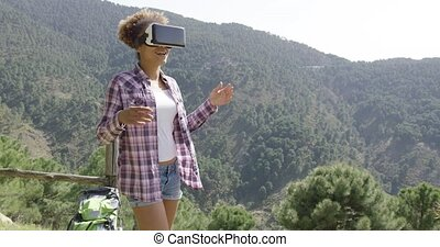 Female backpacker in VR glasses - Young fit woman in casual...