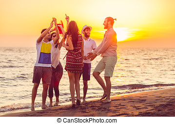 Young People Dancing On Beach at Sunset.