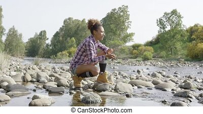 Young woman throwing stones in water - Young woman sitting...