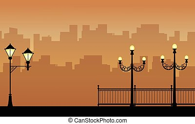 Street lamp with city landscape silhouettes