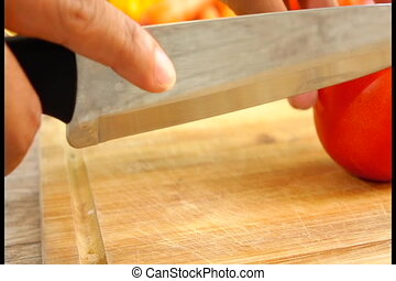 Slincing Tomato in Slow Motion - Close-up of female hands...