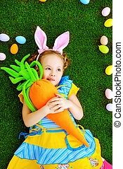 carrot for a bunny - Funny little girl with bunny ears and...