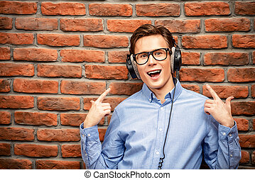 musical hit - Happy young man listens to music in headphones...