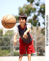 Young boy passing basketball - Young boy in action passing...
