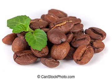 Pile of coffee beans with a mint leaf isolated on white background