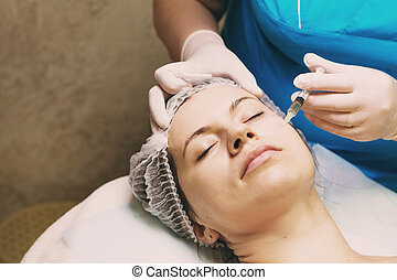 Beautician performs a needle mesotherapy treatment on a...