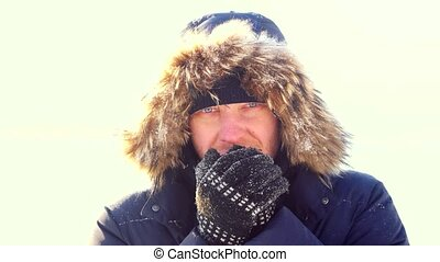 Portrait of young man outdoors freezes looking into the...