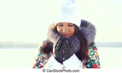 Portrait of young beautiful woman outdoors freezes looking into the camera warms your hands in winter sunny day.