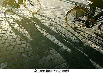 City cyclists, people riding bicycles on cobblestone road