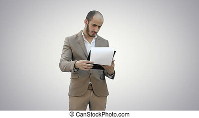 Concentrated businessman reading financial report on white...