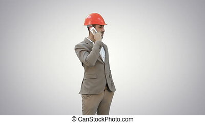 Contractor in hardhat talking on his cell phone on white background.