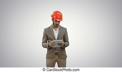 Young architect in helmet holding tablet and showing thumb...