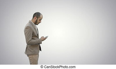 Young man in suit walking and sending text message on mobile phone on white background.