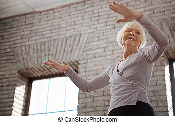 Skilled aging woman performing in the ballroom