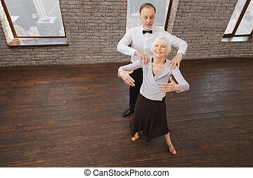 Involved elderly couple performing in interaction in the dance studio