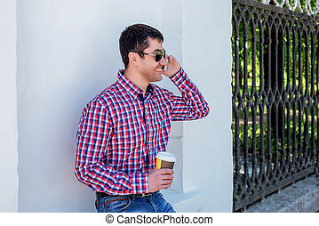 man in shirt and jeans glasses, talking on the phone,...