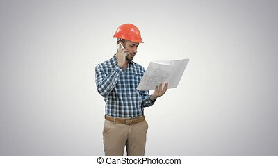 Site manager talking on the phone holding blueprints on...