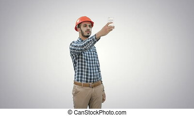 Construction worker using phone to take selfies on white background.