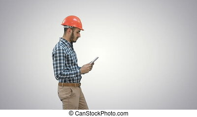 Contractor engineer in hardhat inspecting construction site holding digital tablet on white background.