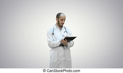 Male doctor in white coat filling in prescription form on...