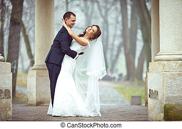 Groom smiles bending over a beautiful bride in a foggy park