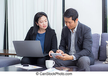 Team of business two people working together on a laptop with during a meeting sitting around a table.