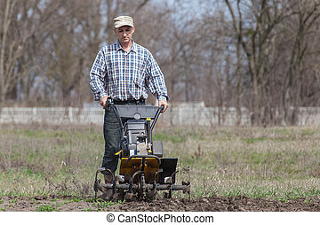 Man loosens the soil cultivator - Man working in the garden...
