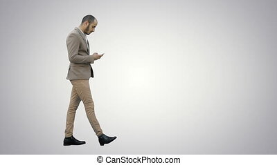 Business man walks in checking up his phone on white background.