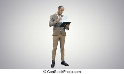 Concentrated businessman reading important report on white...