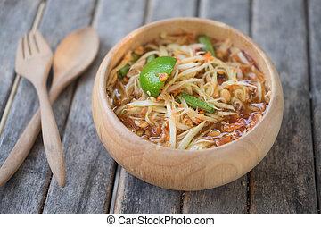 Thai Papaya Salad (Som tum Thai) in wood bowl