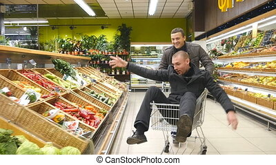 Young man having fun in the shopping mall driving a shopping cart, his friend riding inside. Happy smiling guy sitting in supermarket trolley and going through the grocery store. Slow motion Close up