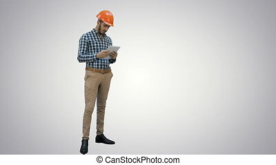Engineer using a wireless tablet to check construction project on white background.