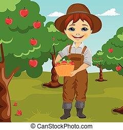 farmer little boy picking apples holding basket standing in...