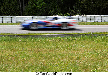 race car - blured motion vintage corvette racing at the...