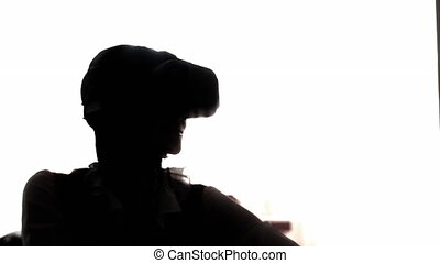 Silhouette young woman playing game using VR-helmet for smart phones. Augmented reality device allows to deep into virtual space