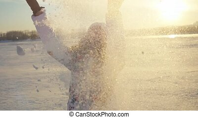 Happy beautiful woman having fun and throwing the snow in winter field on sunset city background in slow motion with lense flare effects.